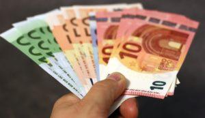 Hand hält aufgefächerte Geldscheine
