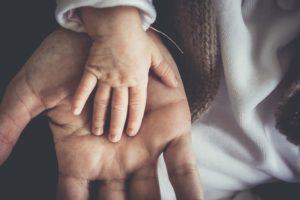 Kinderhand liegt in erwachsener Hand